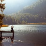woman meditating by a lake